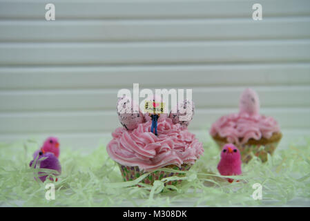 Easter time pink cupcake with egg decorations and miniature person figurine on top with a sign of I love Easter - Stock Photo