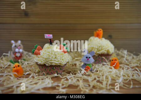 Easter cupcake with miniature person on top with a happy love sign board and decorations - Stock Photo