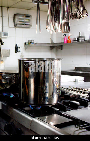 Large steel professional pan on the stove with fire in restaurant kitchen - Stock Photo