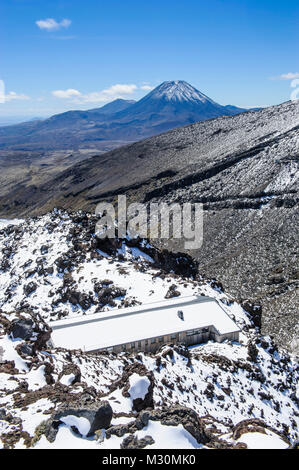 View from Mount Ruapehu on Mount Ngauruhoe with a ski cottage in  the foreground. Unesco world heritage sight Tongariro - Stock Photo