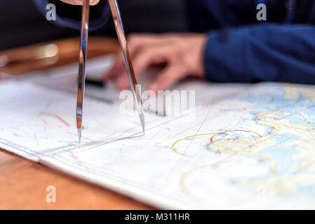 navigation with sea charts in the chart room on a sailing yacht - Stock Photo