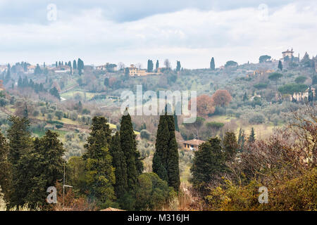 Hilly green Tuscan landscape with cypress trees near Florence in the cloudy evening