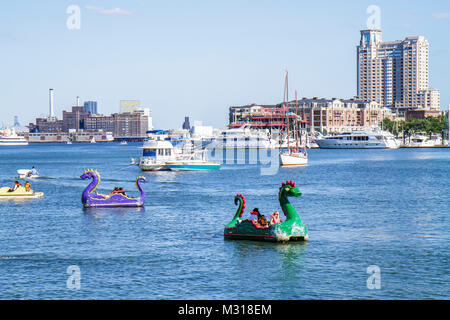 Baltimore Maryland Inner Harbor skyline Patapsco River port waterfront Harborplace attraction paddle boat ride dragon - Stock Photo