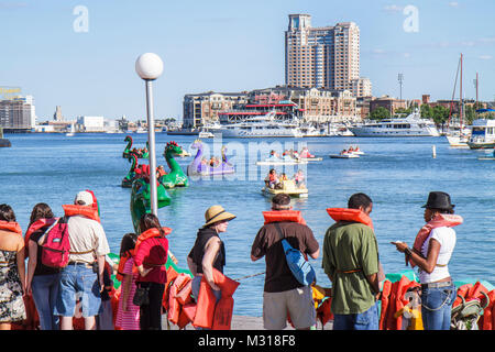 Baltimore Maryland Inner Harbor Patapsco River port waterfront Harborplace paddle boat ride dragon boat skyline - Stock Photo