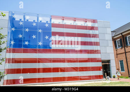 Baltimore Maryland East Pratt Street Star Spangled Banner Flag House building facade red white and blue woman walking - Stock Photo