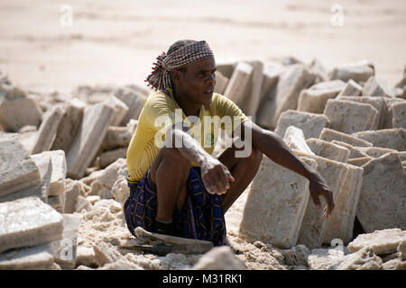 An ethnic Afar man takes a break from mining salt in the Danakil Desert, Ethiopia. - Stock Photo