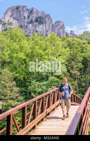 Hiker crossing a bridge at Spruce Knob National Recreation Area. The highest point in West Virginia is at the summit - Stock Photo