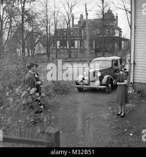 Sericeman and girl have picture taken outside the house in Nova Scotia, ca. 1938. - Stock Photo