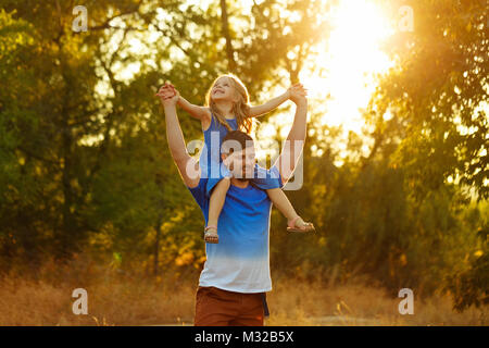 Family time. The father holds the daughter on the shoulders of piggyback. Walk in the park at sunset. They laugh - Stock Photo