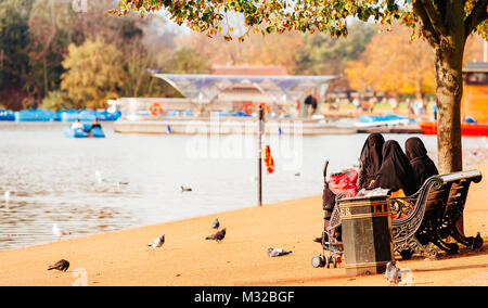 London, UK - October 31, 2014: Muslim woman covered with niqab sitting near Serpentine lake , London. - Stock Photo