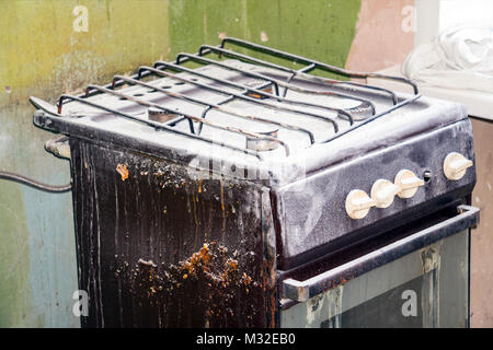 An old dirty gas stove in an abandoned state. Unsanitary conditions - Stock Photo