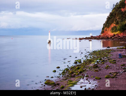 The distinctive redish colour of Shaldon beach on the Teign estuary at dusk looking towards famous Ness. - Stock Photo