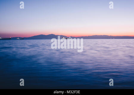 sea view from the port of salonicco at sunset with a boat on the background - Stock Photo