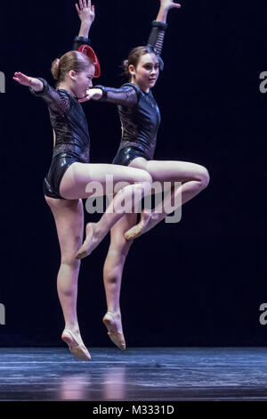 Twelve year old girls dancing onstage doing a pose jump - Stock Photo