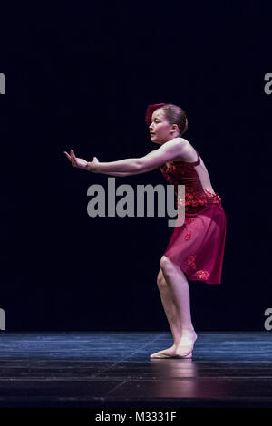 Twelve year old girl performing a solo lyrical dance onstage, conveying sadness and guilt - Stock Photo