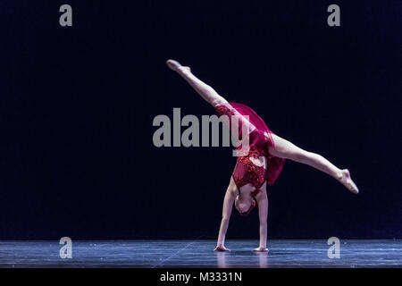 Twelve year old girl performing a solo lyrical dance onstage, doing a cartwheel to the floor - Stock Photo