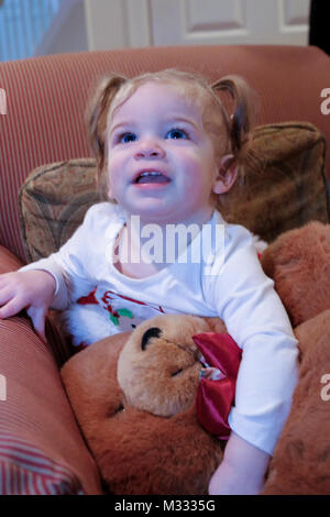 13-month old girl playing with a large stuffed bear - Stock Photo