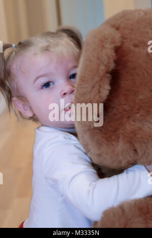 13-month old girl hugging a large stuffed bear - Stock Photo