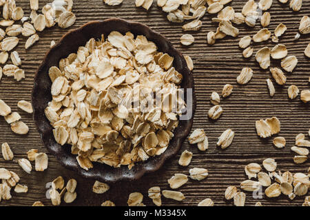 Ceramic Bowl of Rolled Oats on Rustic Wooden Table - Stock Photo