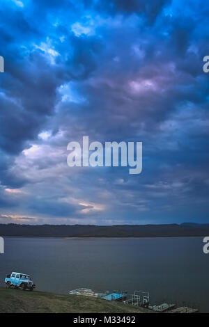 Four wheel drive car parked on the shore of an argentinian lake during dramatic sunset, Salta region in northern - Stock Photo