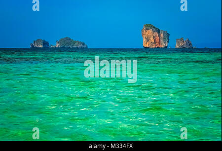 Torquise sea waters and impressive karst formations on the coast of Thailand near Krabi - Stock Photo