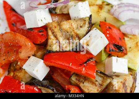 Grilled vegetables salad with red bell pepper, eggplant, onions, feta cheese, peppers, cilantro and tomato. - Stock Photo
