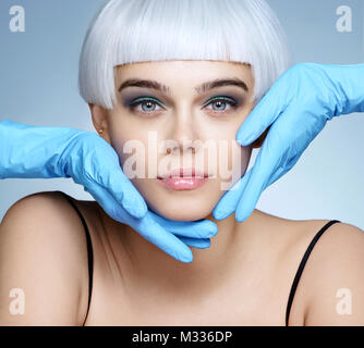 Doctor's hands in gloves touching face of beautiful woman. Photo of fashion blonde model after cosmetic injection. - Stock Photo