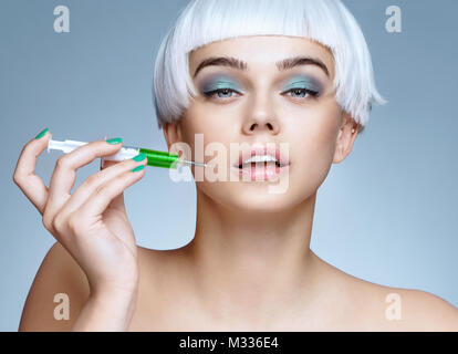 Beautiful woman face with syringe makes cosmetic injection in the lips. Clean Beauty concept - Stock Photo
