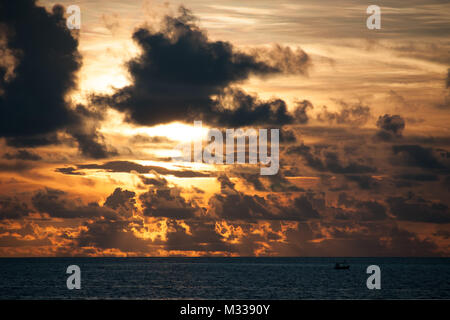 Bright orange sunset sky over the ocean with dark dramatic clouds scattered over the horizon, dark sea water.