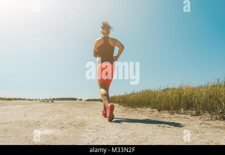 Young woman jogging cross-country running in summer seaside.  Concept fitness and healthy lifestyle - Stock Photo