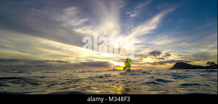 TSgt. Alfred Van Gieson of 735th Air Mobility Squadron at Hickam Field paddles his outrigger canoe into the sunset - Stock Photo
