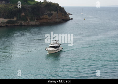 A white yacht entering the Old Port or Vieux Port in Marseille France. The rocky coastline and a sailboat are in - Stock Photo