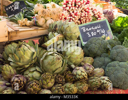 A vegetable stand in Aix en Provence France selling broccoli, artichokes, radishes, carrots, scallions and cabbage. - Stock Photo
