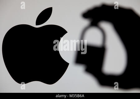 LONDON, UK - MAY 15th 2017: Apple security issues. Silhouette of a hand holding a padlock infront of the apple logo - Stock Photo
