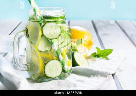 Summer fresh water detox with lemon, cucumber, ice and mint in mason jar on a white wooden background. - Stock Photo