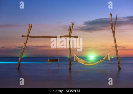 Wooden swing and hammock on the beach of Koh Kood island in Thailand. - Stock Photo