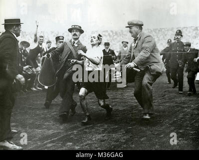 DORANDO PIETRI (1885-1942) Italian long distance runner at the finish of the 1908 Olympics Marathon helped by Dr - Stock Photo
