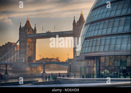 London UK. 24 Jan 2017. Dawn breaks behind Tower Bridge and the GLA building in central London. Credit: Malcolm - Stock Photo