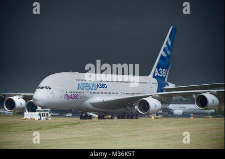 Airbus A380 on the runway against dark grey sky at the Farnborough International airshow before a storm breaks. - Stock Photo