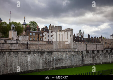 The outer curtain wall and dry moat of Tower of London - historic castle and popular tourist attraction on the north - Stock Photo