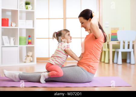 Mom and child doing fitness exercises on mat at home - Stock Photo