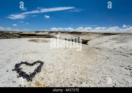 stone heart made of red pebbles in the New Mexico desert on a dry and barren dirt ground - Stock Photo