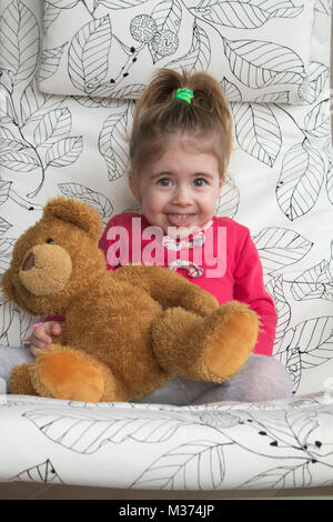 Clouse-up portrait of cheerful little girl gesturing and making funny grimace at camera. - Stock Photo