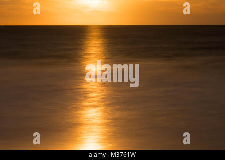 full moon rising over a calm and shimmering ocean in a golden night sky - Stock Photo