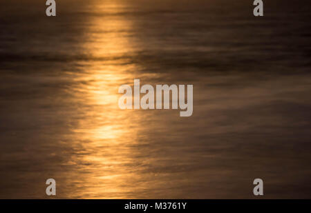 abstract background view of a beautiful full moon rising over a shimmering ocean - Stock Photo