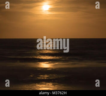 full moon rising into a warm and milky night sky over the ocean - Stock Photo