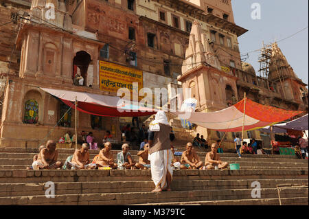 Holymen sit on steps in Varanasi, India - Stock Photo