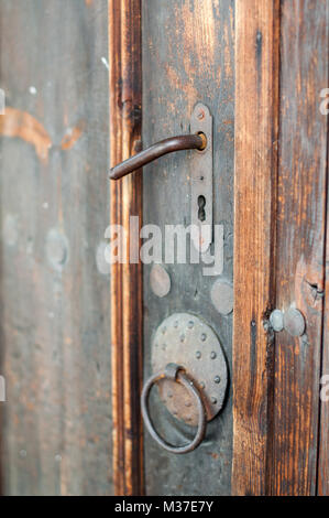 Old fashioned Rusty lock in ancient wooden door - Stock Photo