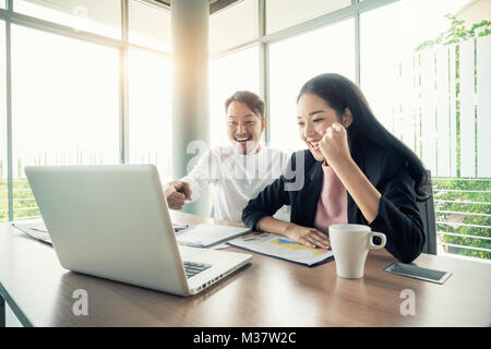 Asian couple business people with casual suit working with happy action in office Business people concept. - Stock Photo