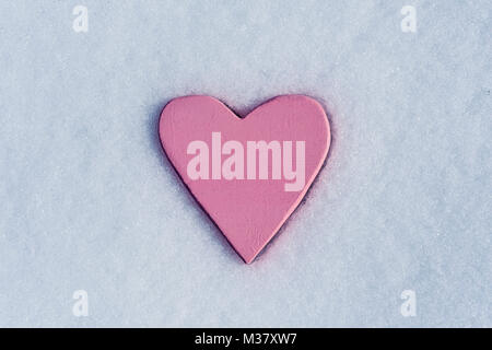 closeup of a pink heart on the snow, with some blank space around it - Stock Photo